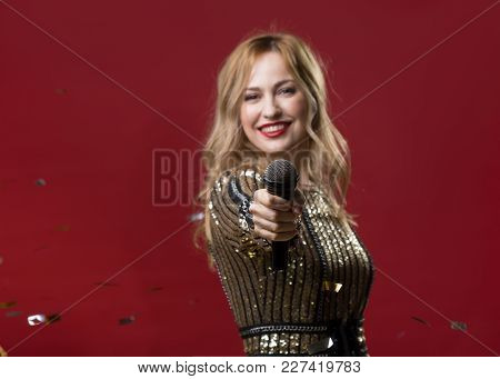 Waist Up Portrait Of Smiling Female Person Stretching Hand With Mike. Focus On Transmitter. Copy Spa