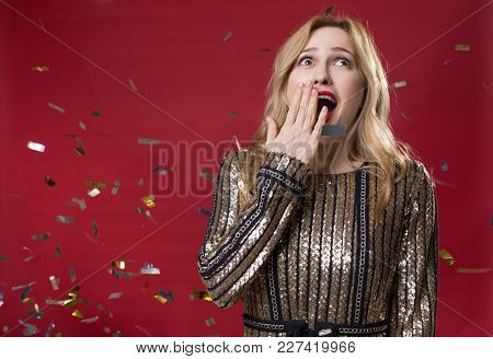 Waist Up Portrait Of Astonished Female In Festive Clothes Covering Mouth Opened With Pleasure. Copy