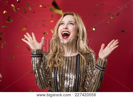Waist Up Portrait Of Good Looking Triumphing Lady Looking Up At Confetti. Isolated On Red Background