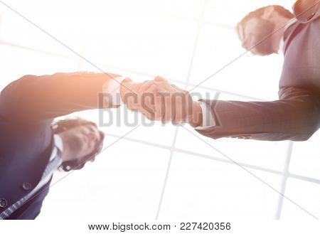 Two business people are holding hands to business cooperation.
