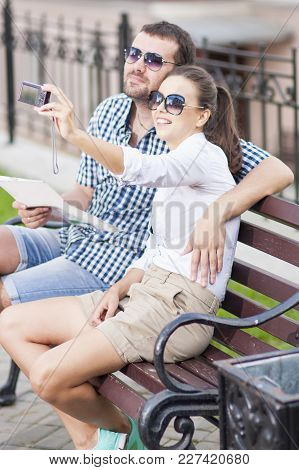 Traveling  Concepts. Smiling And Happy Caucasian Couple In Love Sitting On Bench Outdoors While Taki