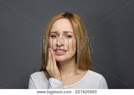 Dental Treatment. Portrait Of Joyless Female Holding Her Hand On Cheek And Wincing In Pain. Isolated