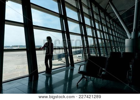 Moscow - May 15, 2017: Female Traveler Looks Out The Window At The Airport Terminal. Young Woman Is
