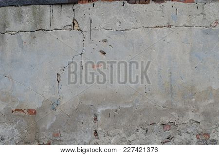 Old Grey Concrete Garage Wall With Red Bricks And Cracks Abstract Background