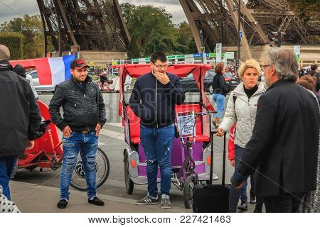 Paris, France - October 08, 2017 : Rickshaw Drivers Wait For Customers Next To The Eiffel Tower On A