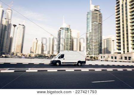 Van Going Fast, Dubai Skyscrapers In The Background. Panning Shot With Motion Blur.