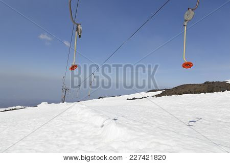 Alpine Ski Lift At Etna Ski Resort. Two Lines With Red Disks And Mountain Background. Sicily, Italy.