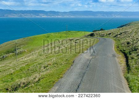 Old Asphalt Road Leads Through Green Fields Down To The Ocean With Hills In The Background