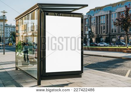 Vertical Blank White Billboard At Bus Stop On City Street. In The Background Buildings And Road. Moc