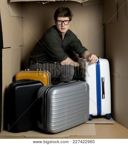 Travel Concept. Full Length Portrait Of Serious Young Man Is Sitting With Bags Inside Small Cardboar