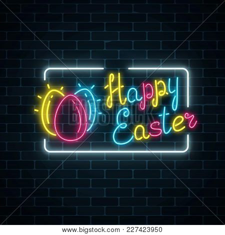 Glowing Neon Happy Easter Signboard With Eggs And Lettering On Dark Brick Wall Background. Easter Fu