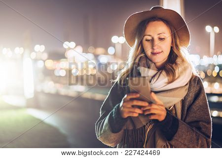 Autumn Evening. Young Woman In Hat And Scarf Stands On City Street And Uses Smartphone. Hipster Girl