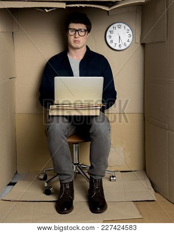 Still At Work Concept. Full Length Portrait Of Young Unhappy Employee Is Sitting At Table In Cramped