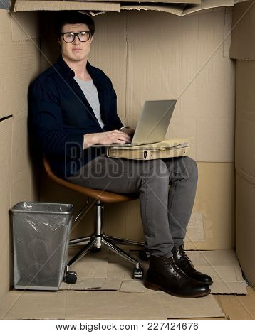 Too Closely Concept. Full Length Portrait Of Confused Businessman Is Sitting In Cramped Carton Offic