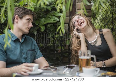 Young Men Is Bored And Stressed With His Companion Having Too Much Fun On The Phone, Ignoring Him Co