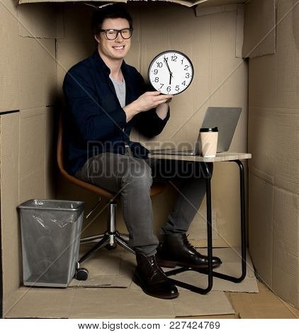 End Of Working Day. Full Length Portrait Of Positive Young Manager Is Sitting At Table Cramped Paper