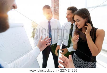 businessman pointing business team on a blank flipchart.