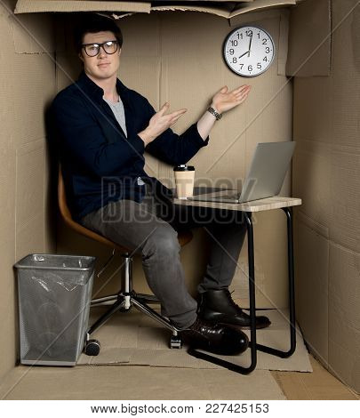 Overtime Concept. Full Length Portrait Of Unhappy Young Manager Is Sitting At Table In Cramped Cardb