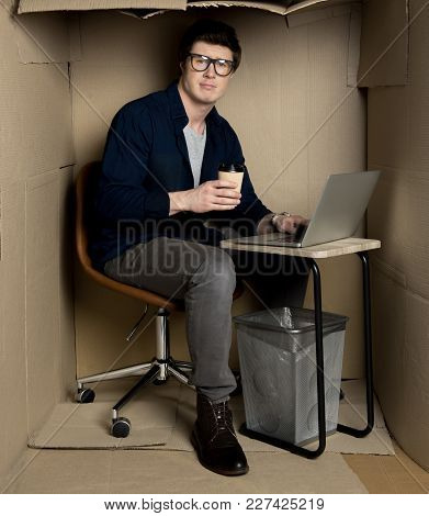 Feeling Uncomfortable Concept. Full Length Portrait Of Manager Is Sitting At Table In Cramped Carton