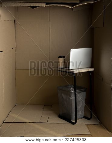 Little Space Concept. Empty Cramped Cardboard Office With Small Table And Modern Laptop On It
