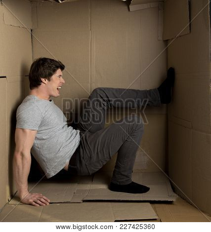 Cramped Space Concept. Full Length Of Annoyed Guy Is Sitting In Narrow Cardboard Box While Screaming