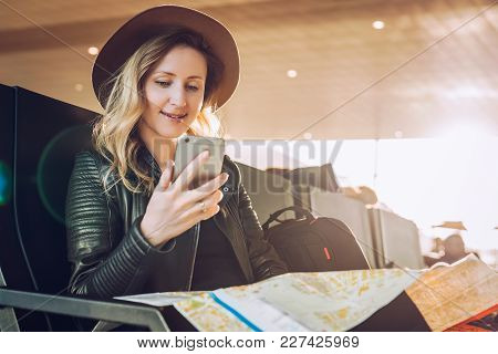 Young Woman Tourist In Hat, With Backpack Sits At Airport, Uses Smartphone, Holding Destination Map.