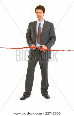 Full Length Portrait Of Smiling Modern Businessman Cutting The Red Ribbon. Concept - Grand Opening