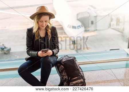 Young Woman Tourist In Hat, With Backpack Sits At Airport Near Window And Uses Smartphone. In Backgr
