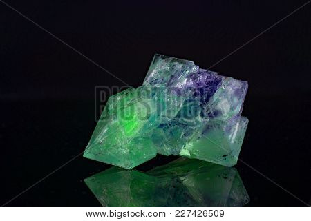 Green natural crystal mineral on a black background
