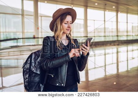 Young Tourist Woman In Hat, With Backpack Stands At Airport And Uses Smartphone.hipster Girl Checks