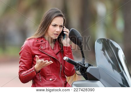 Angry Motorbiker Calling Insurance Assistance On A Mobile Phone Sitting On A Motorbike