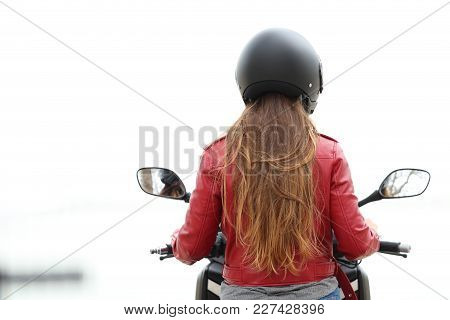 Back View Of A Motorbiker Sitting On A Motorcycle On White Background