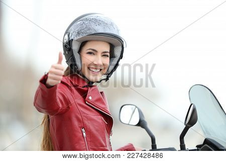 Satisfied Motorbiker Gesturing Thumbs Up On Her Motorcycle Outdoors