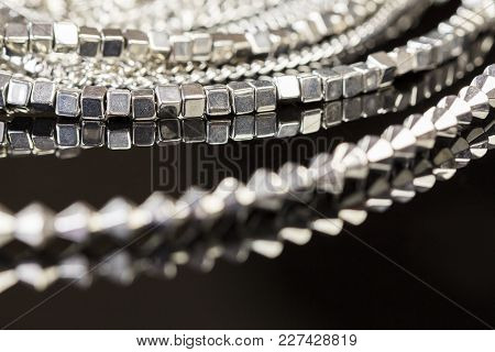 Pile Of Assorted Silver Chains With Shiny Box Chains, Cube Chains And Ordinary Linked Chain On A Gre