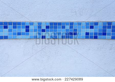 Blue Mosaic Tiles Line At White Wall
