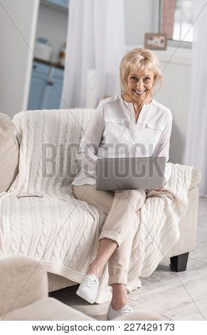 Progressive Lady. Jolly Glad Mature Woman Carrying Laptop While Smiling And Looking At Camera