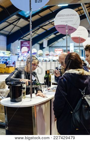 Strasbourg, France - Feb 19, 2018: Woman Pouring Wine To Customers Tasting And Buying French Wine At
