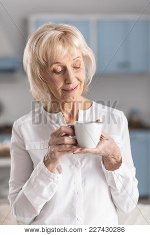Coffee Aroma. Attractive Reflective Mature Woman Looking Down While Holding Cup And Enjoying Morning