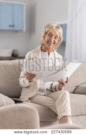 Accurate Report. Happy Jolly Mature Businesswoman Posing On Couch While Scrutinizing Papers And Smil