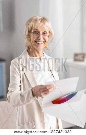 Love My Work. Gay Jolly Mature Businesswoman Standing While Holding Documentation And Smiling