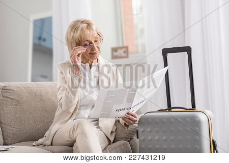 Bon Voyage. Thoughtful Pleasant Mature Woman Sitting On Couch While Scrutinizing Article And Touchin