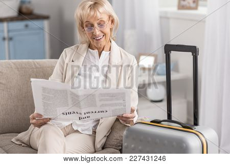 Ready To Go. Optimistic Happy Mature Woman Sitting Near Suitcase While Holding Newspaper And Wearing