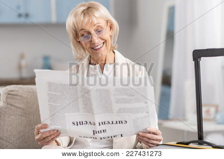 Breaking News. Confident Attractive Mature Woman Smiling While Examining Article And Putting On Glas