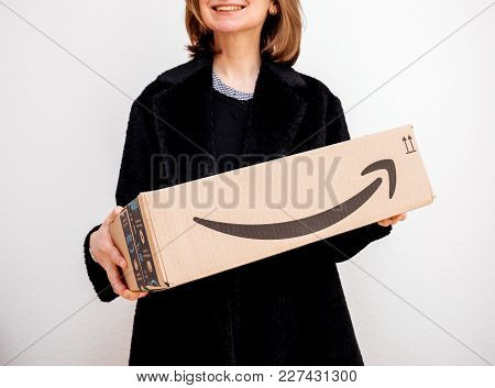 Paris, France - Feb 16, 2018: Smiling Elegant Fashionista Woman Holding Amazon Prime Cardboard Parce