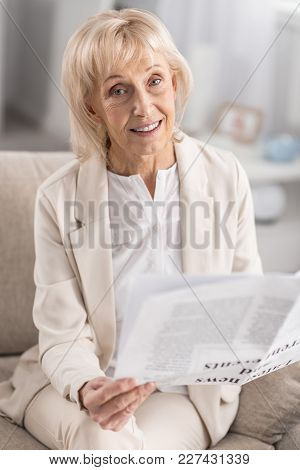 Be Aware. Nice Glad Mature Woman Gazing At Camera While Having Newspaper And Sitting