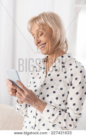 Waiting Response. Glad Elegant Mature Woman Responding Message While Looking At Screen And Posing On