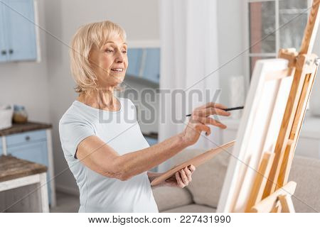 My Masterpiece. Smart Mature Woman Standing In Front Of Easel While Looking At It And Painting