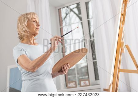 I Change This. Glad Appealing Mature Woman Staring At Easel While Posing In Profile And Rising Tasse