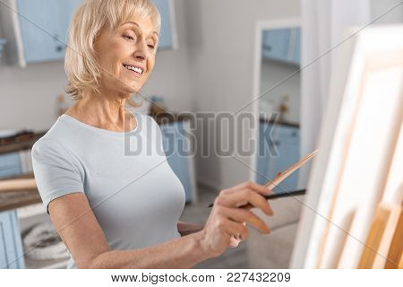 Never Late. Optimistic Vigorous Mature Woman Moving Tassel And Smiling While Drawing