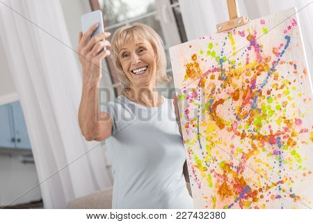 My Talent. Jolly Optimistic Mature Woman Taking Selfie While Smiling And Staying Near Easel